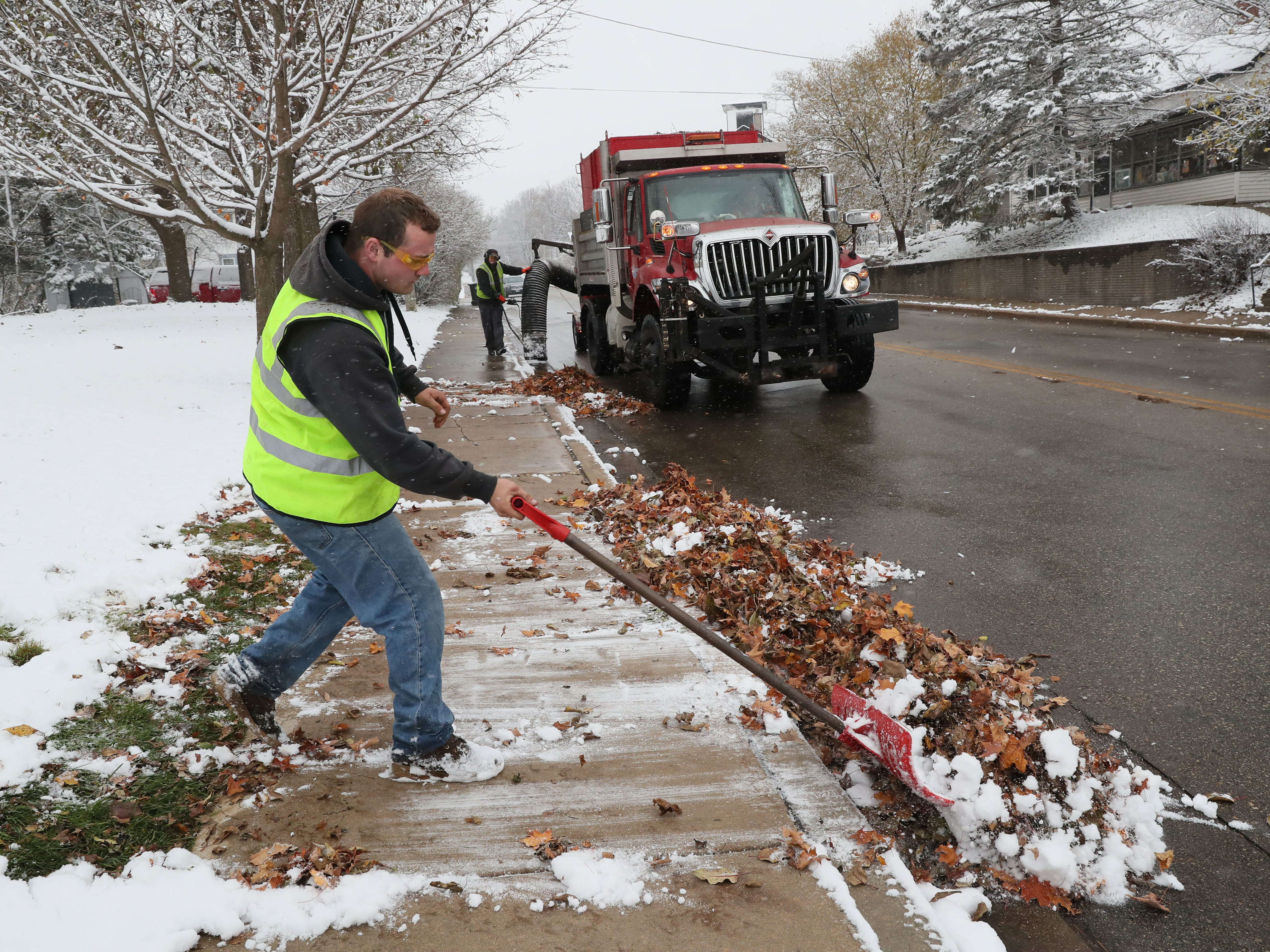 Jarrett Schmitz (left) shovels snow-covered leaves into the street along Prospect Avenue in the Village of Pewaukee as Dan Greig vacuumsd them up. Both men work for the Village of Pewaukee.
