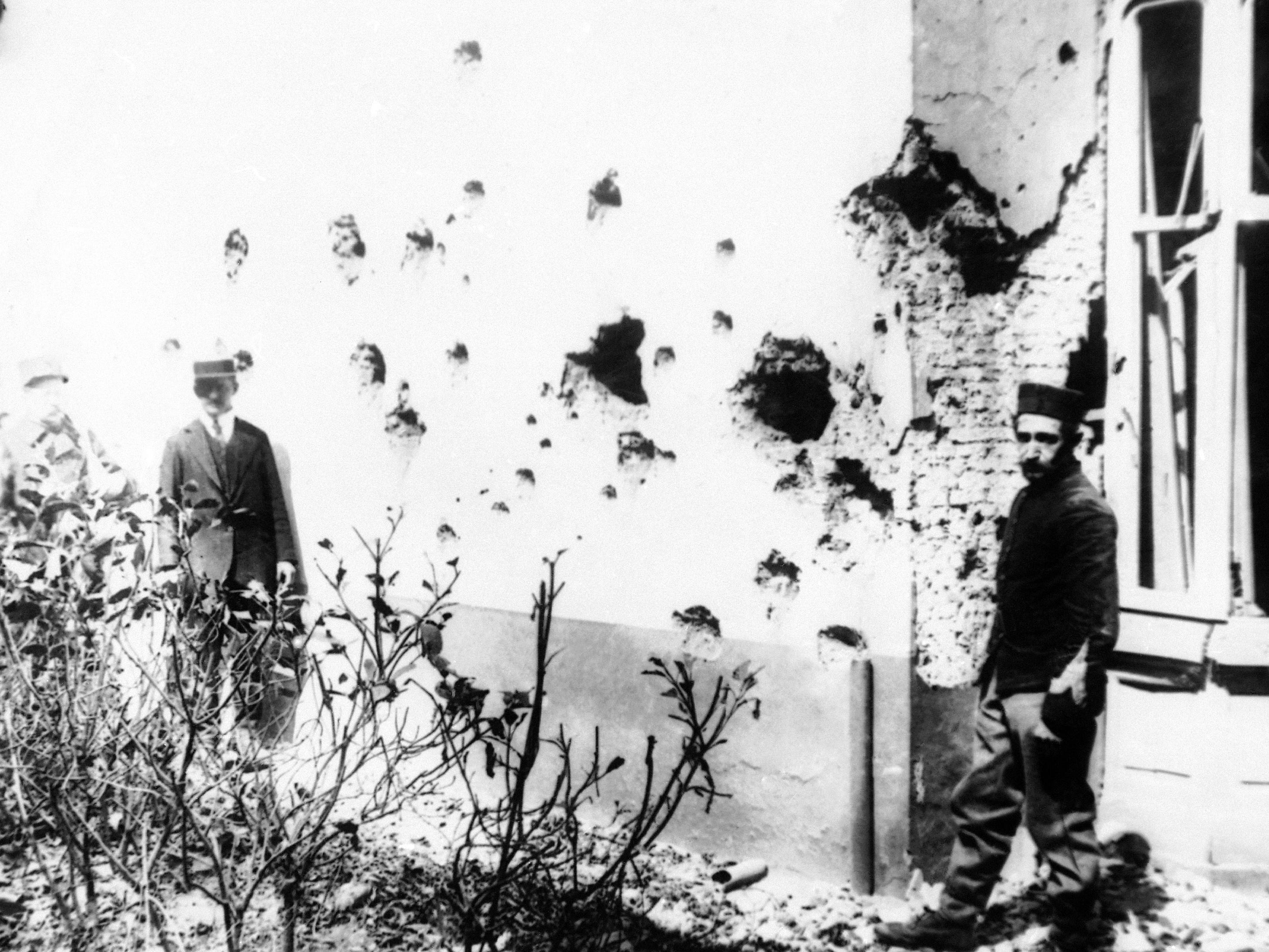 In this 1914 photo, a man stands next to a building damaged by shrapnel from bombs dropped from a zeppelin in Antwerp, Belgium. Antwerp was damaged heavily during World War I.