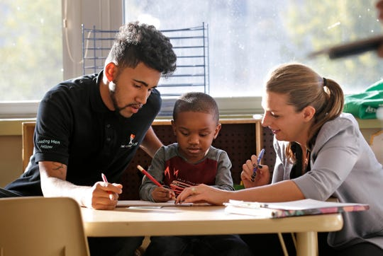 Patrick Jagiello instructs Tarrell Harvey on how to write the letters of his name. assisted by literacy coach Rebecca Pride. Jagiello is working  as part of a new program called the Leading Men Fellows, aimed at training young men of color to become early childhood teachers.
