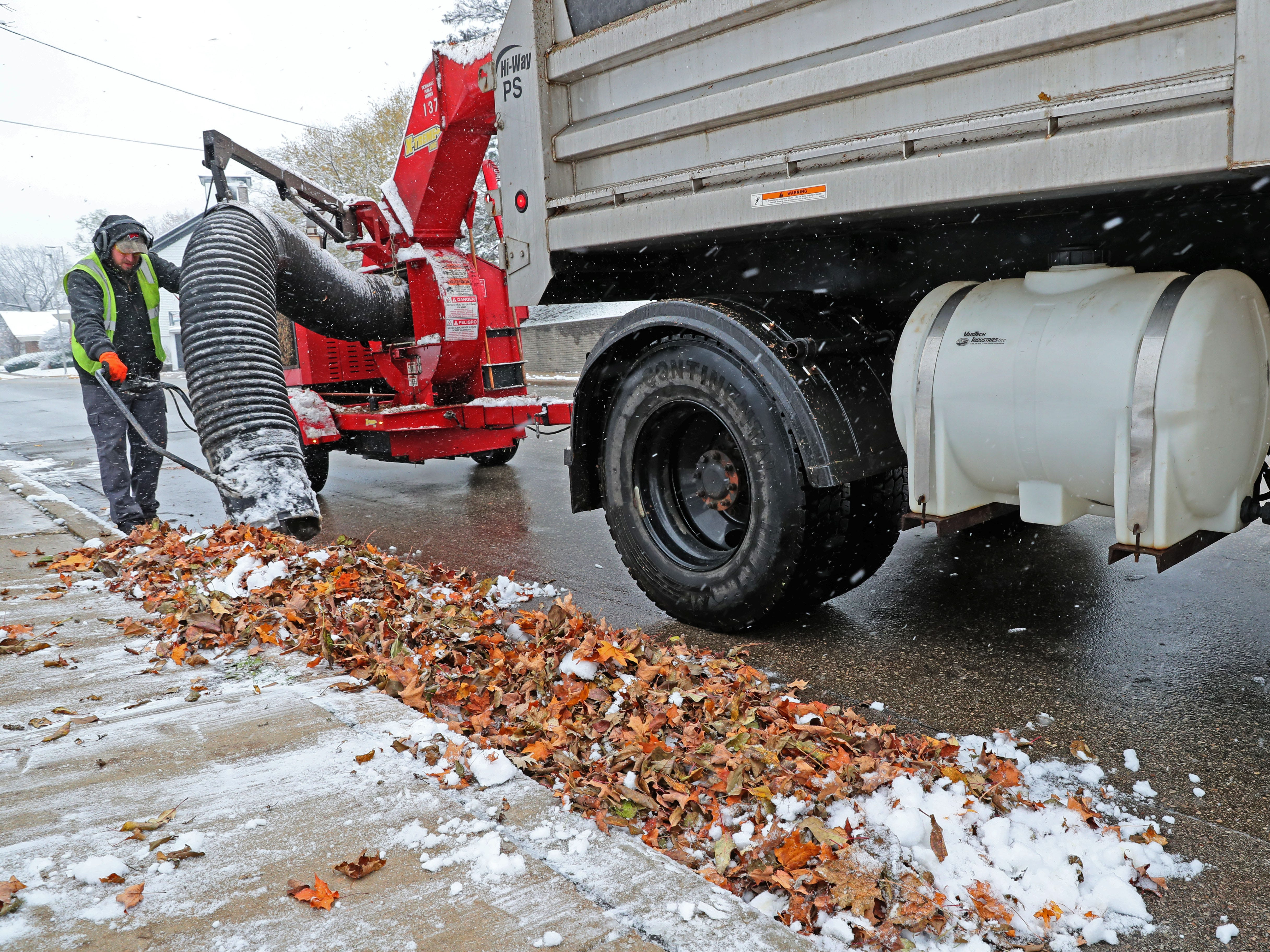 Dan Greig vacuums wet leaves into a truck along Prospect Avenue in  Pewaukee.