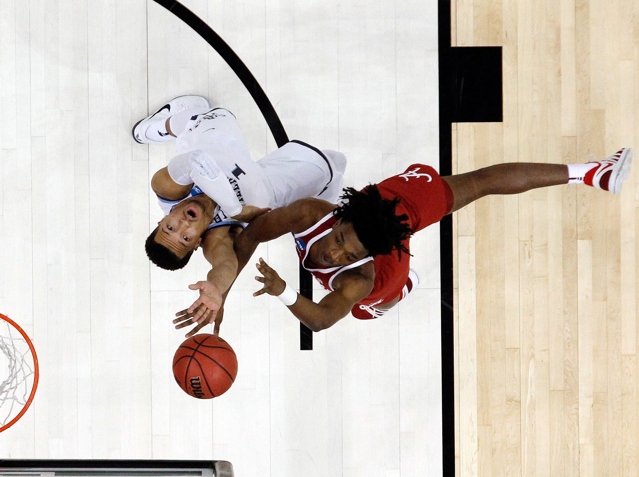 Mar 17, 2018; Pittsburgh, PA, USA;  Alabama Crimson Tide guard Dazon Ingram (12) shoots over Villanova Wildcats guard Jalen Brunson (1) during the first half in the second round of the 2018 NCAA Tournament at PPG Paints Arena. Villanova won 81-58. Mandatory Credit: Charles LeClaire-USA TODAY Sports