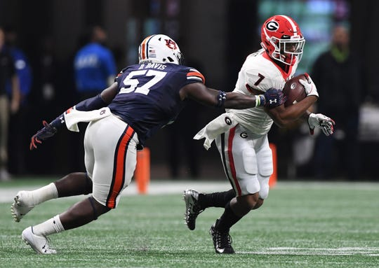 Georgia running back D'Andre Swift (7) runs the ball against Auburn linebacker Deshaun Davis (57) during the SEC Championship game at Mercedes-Benz Stadium on Dec. 2, 2017, in Atlanta.