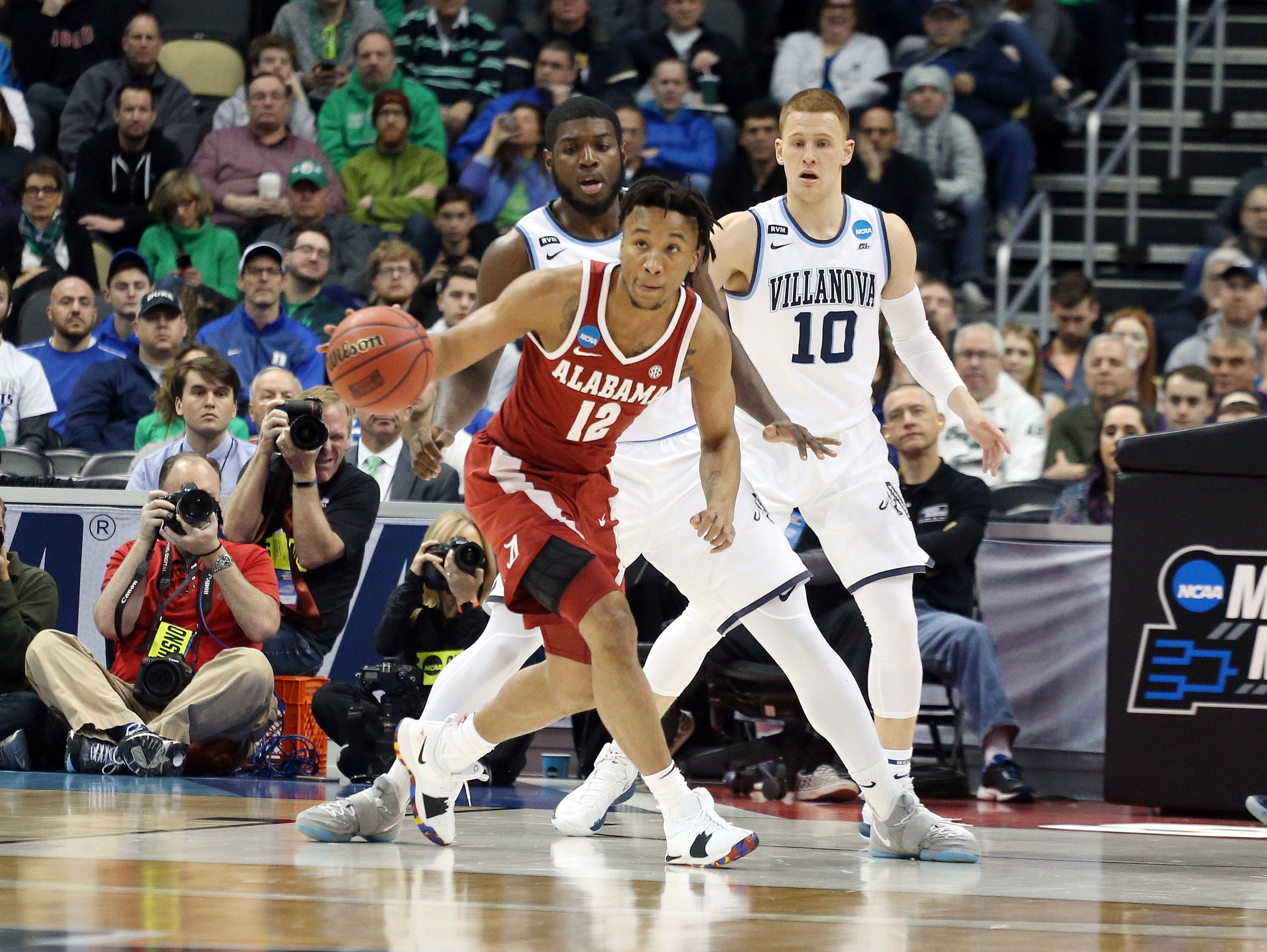 Mar 17, 2018; Pittsburgh, PA, USA;  Alabama Crimson Tide guard Dazon Ingram (12) handles the ball as Villanova Wildcats forward Eric Paschall (4) and guard Donte DiVincenzo (10) defend during the first half in the second round of the 2018 NCAA Tournament at PPG Paints Arena. Villanova won 81-58. Mandatory Credit: Charles LeClaire-USA TODAY Sports