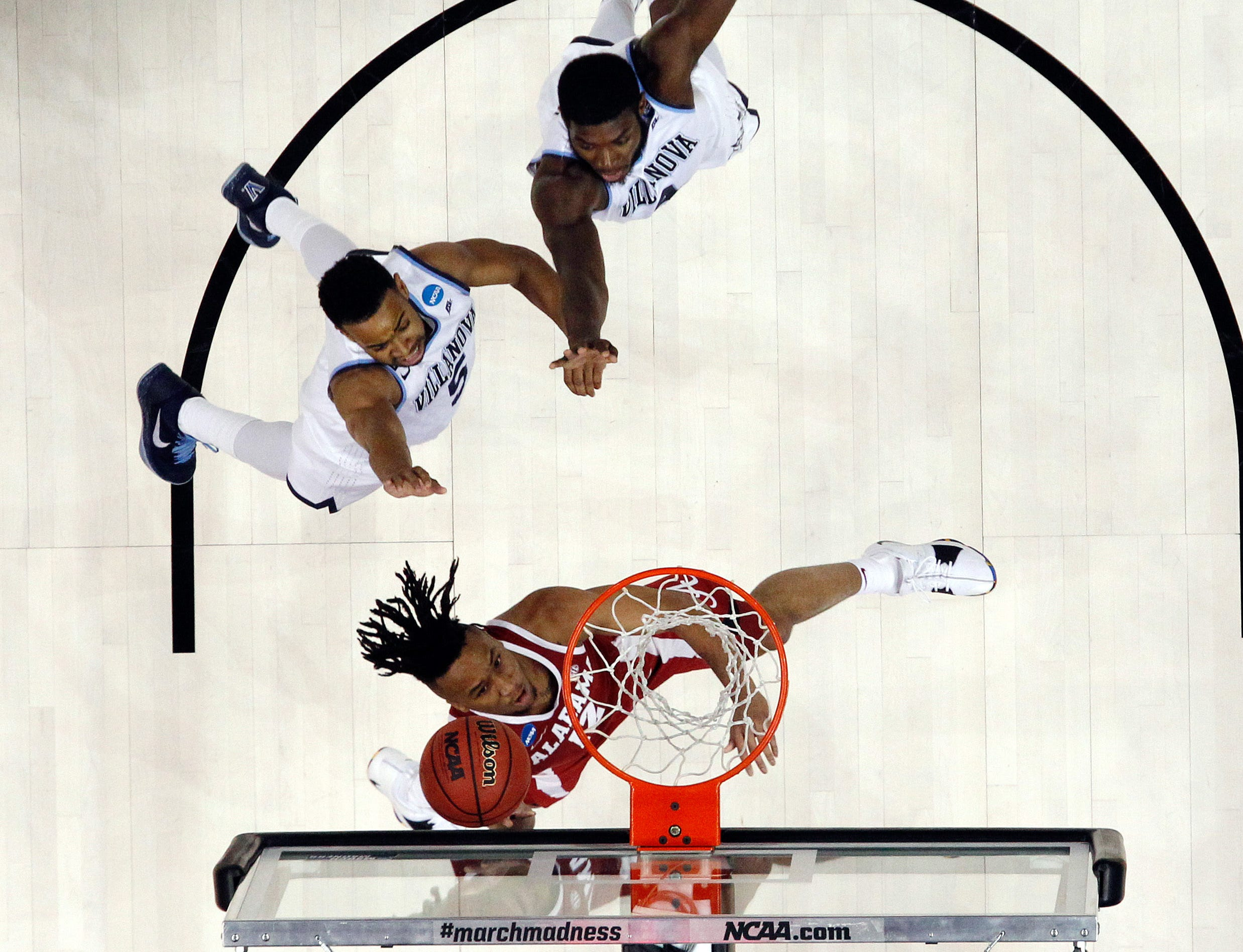 Mar 17, 2018; Pittsburgh, PA, USA;  Alabama Crimson Tide guard Dazon Ingram (12) goes to the basket past Villanova Wildcats guard Phil Booth (5) and forward Eric Paschall (4) during the first half in the second round of the 2018 NCAA Tournament at PPG Paints Arena. Villanova won 81-58. Mandatory Credit: Charles LeClaire-USA TODAY Sports