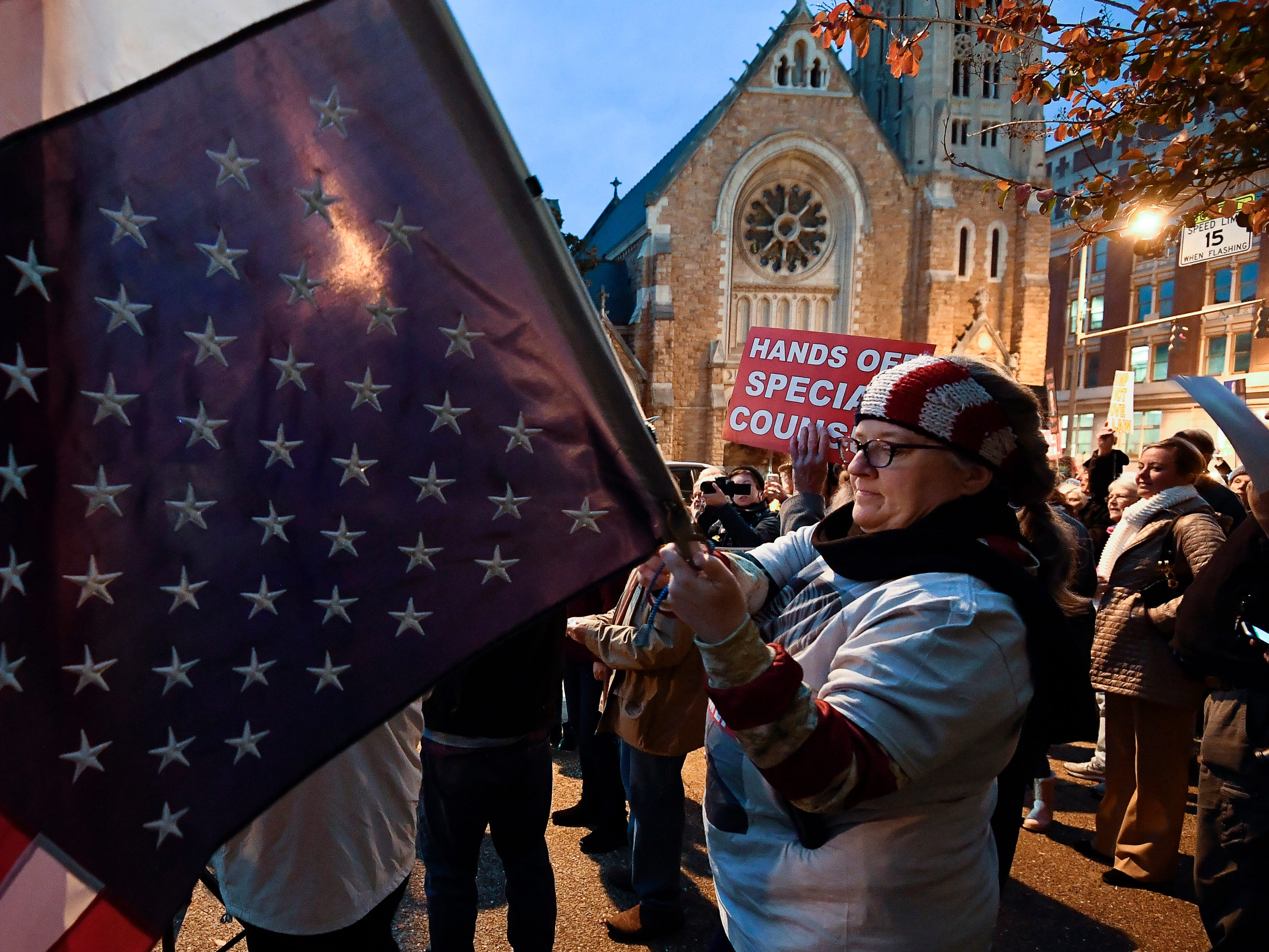 "Jean Wilson waves an upside down flag with protesters for a ""Nobody is Above the Law Rally"" on Broadway outside the Estes Kefauver Federal Building & Courthouse Thursday, Nov. 8, 2018, in Nashville, Tenn."