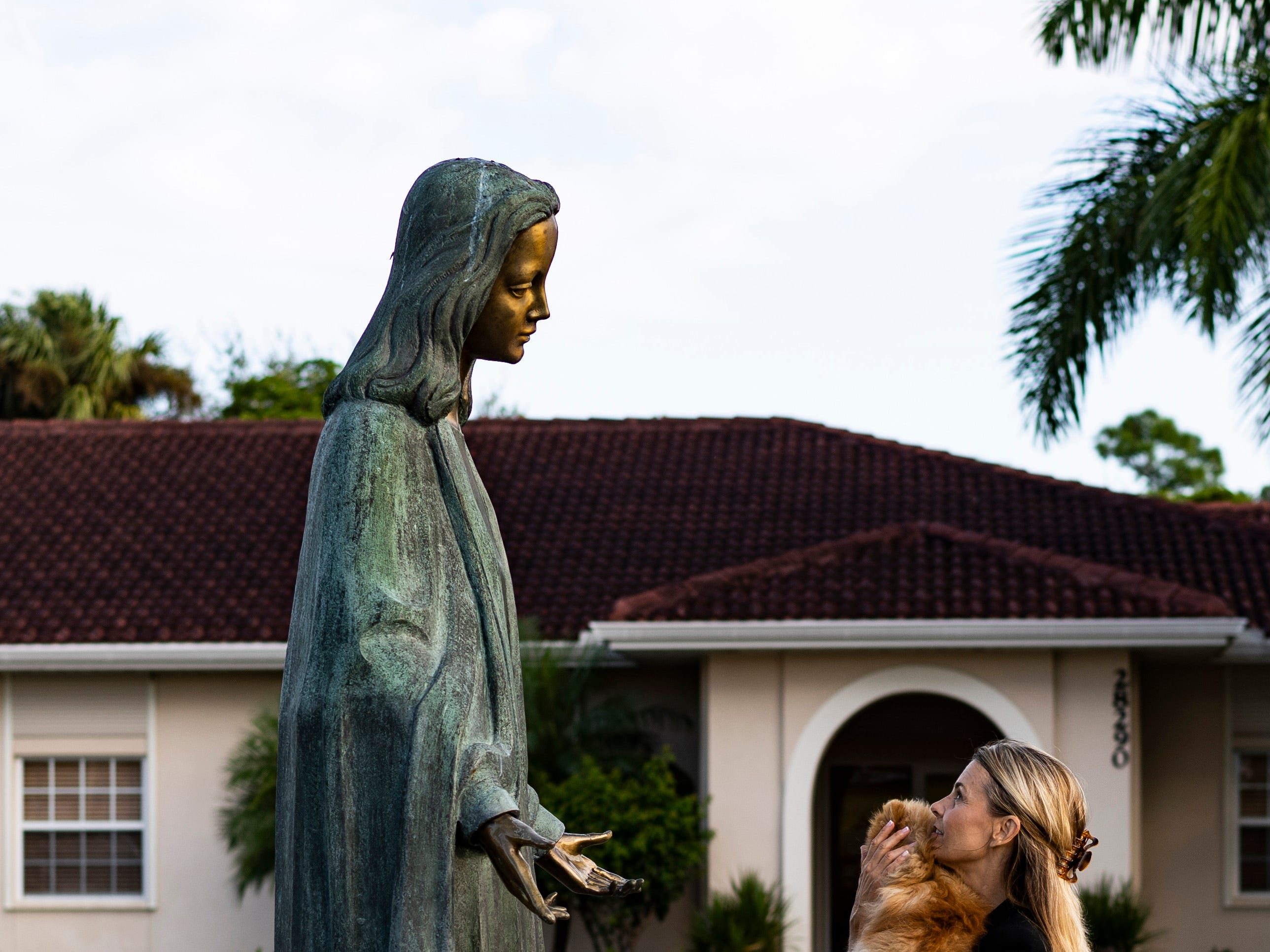 After the blessing ceremony Carrie Caldwell walks up to the  sculpture of Virgin Mary by the front entrance of St. Leo Catholic Church in Bonita Springs, saying her morning prayers while embracing her 9-month-old Pomeranian named Pommie.
