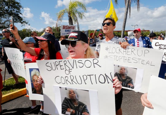 A crowd protests outside the Broward County Supervisor of Elections office Friday, Nov. 9, 2018, in Lauderhill, Fla. A possible recount looms in a tight Florida governor, Senate and agriculture commission race.