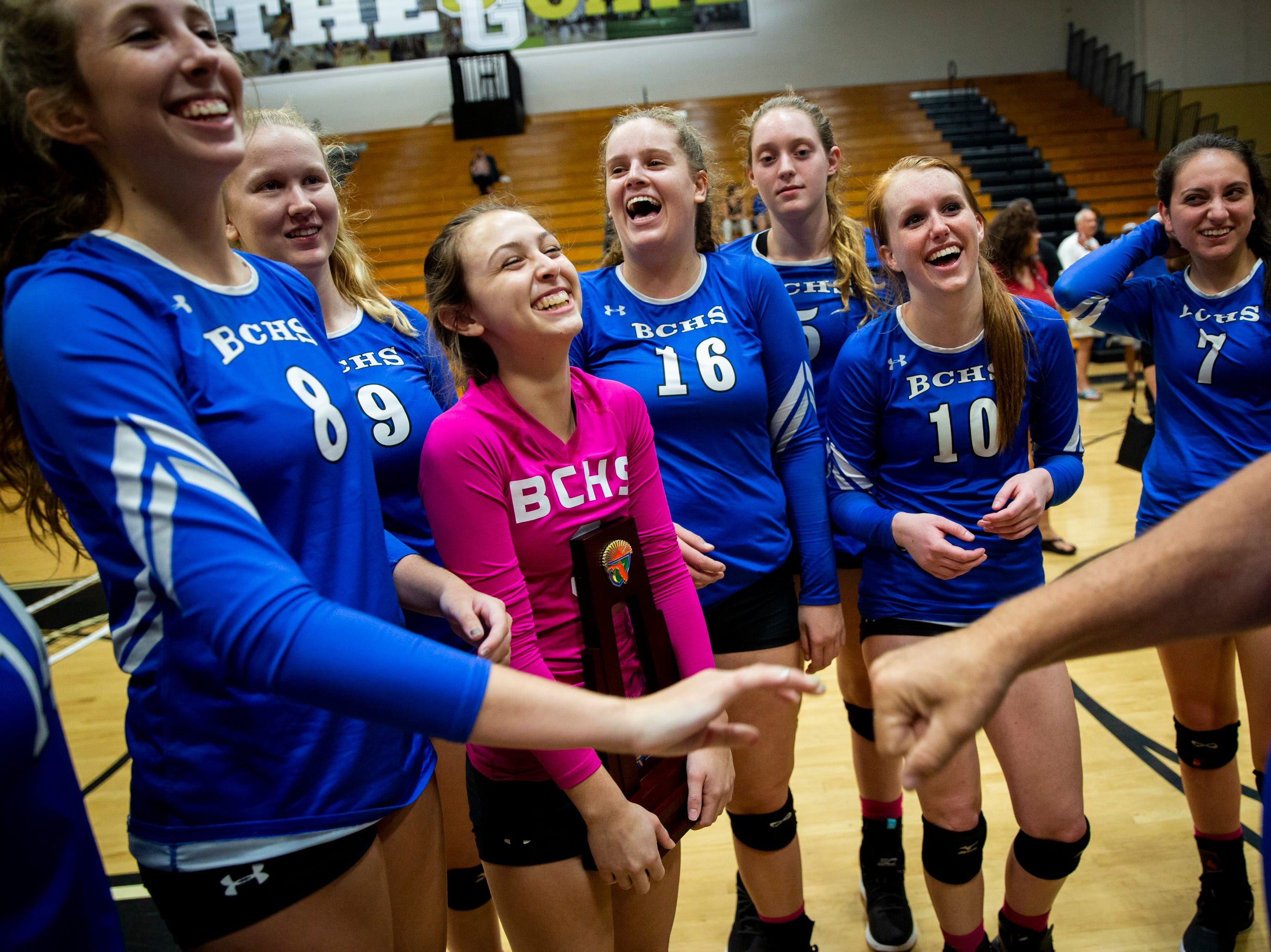 The Barron Collier volleyball team celebrates with activities coordinator Ken Andiorio after sweeping Palmetto Ridge in the Class 7A-District 12 championship volleyball match on Thursday, October 18, 2018, at Golden Gate High School in Naples.