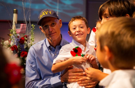 """Gov. Rick Scott, sits surrounded by his grandson, Auguste Guimard,  and the first-grade class from The Village School in Naples. Scott sat answering questions about what it means to be a governor after the Veterans Day event at the school on Nov. 9, 2018. """"When you are a governor, you have a big house, a chef and you get to help people,"""" Scott said."""