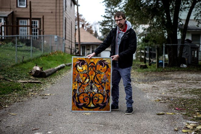 Jonathon Hardy, of JH Stained Glass, poses for a photo outside his studio with a stained glass window he created. Hardy does custom orders as well as repairs.