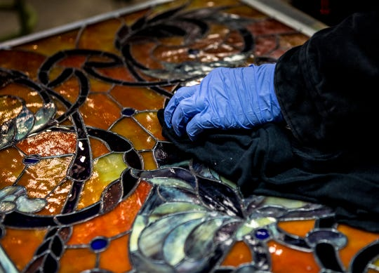 Jonathon Hardy, of JH Stained Glass, polishes a stained glass window he recently finished. Hardy does custom orders as well as repairs.