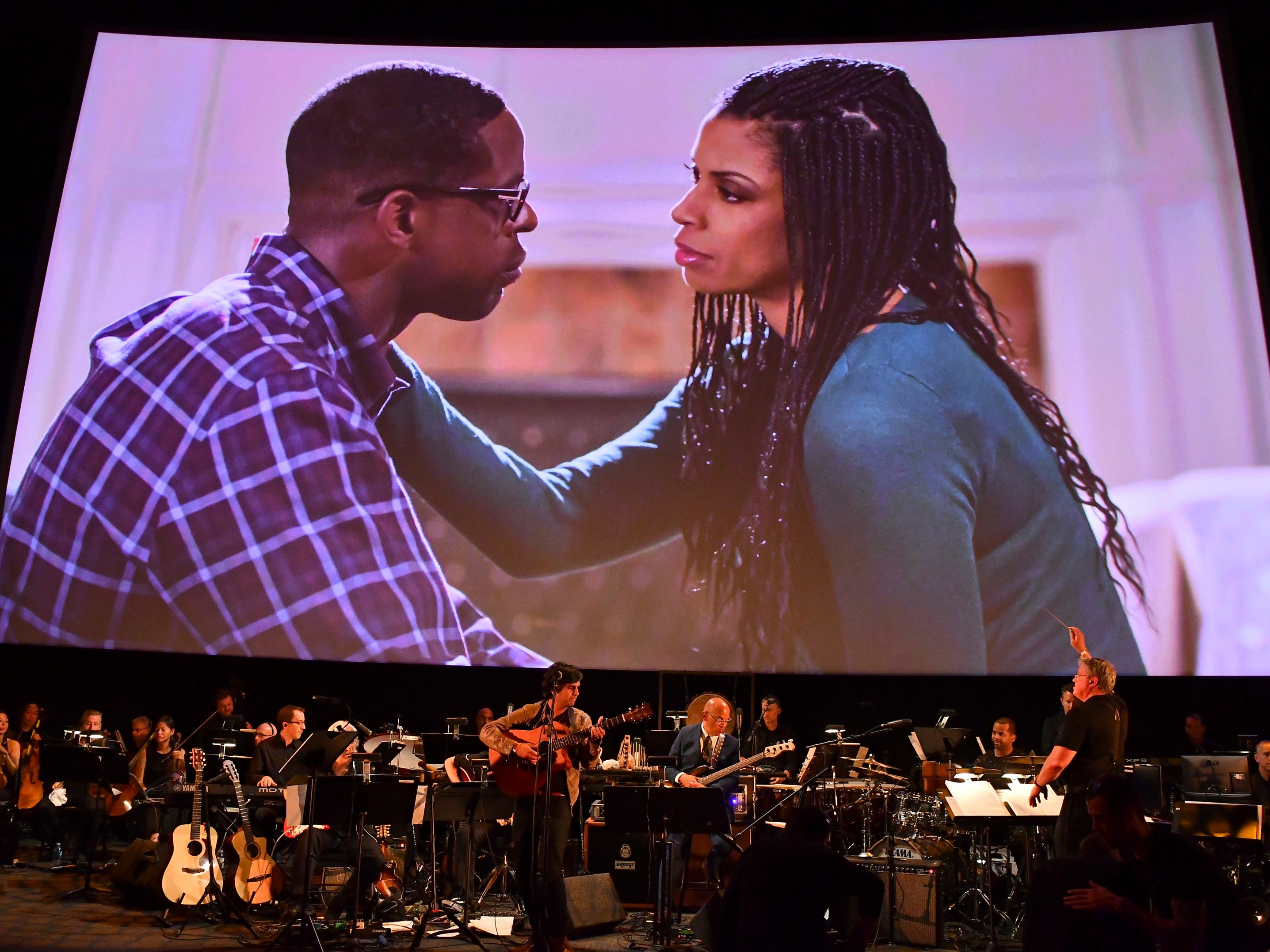 Conductor Mark Watters, right, and composer Siddhartha Khosla, center, perform the score from This Is Us during WORDS + MUSIC, presented Thursday, June 29, 2017 at the Television Academy's Wolf Theatre at the Saban Media Center in North Hollywood, Calif. Sterling K. Brown, left, and Susan Kelechi Watson are pictured on screen. (Photo by Vince Bucci/Invision for the Television Academy/AP Images)