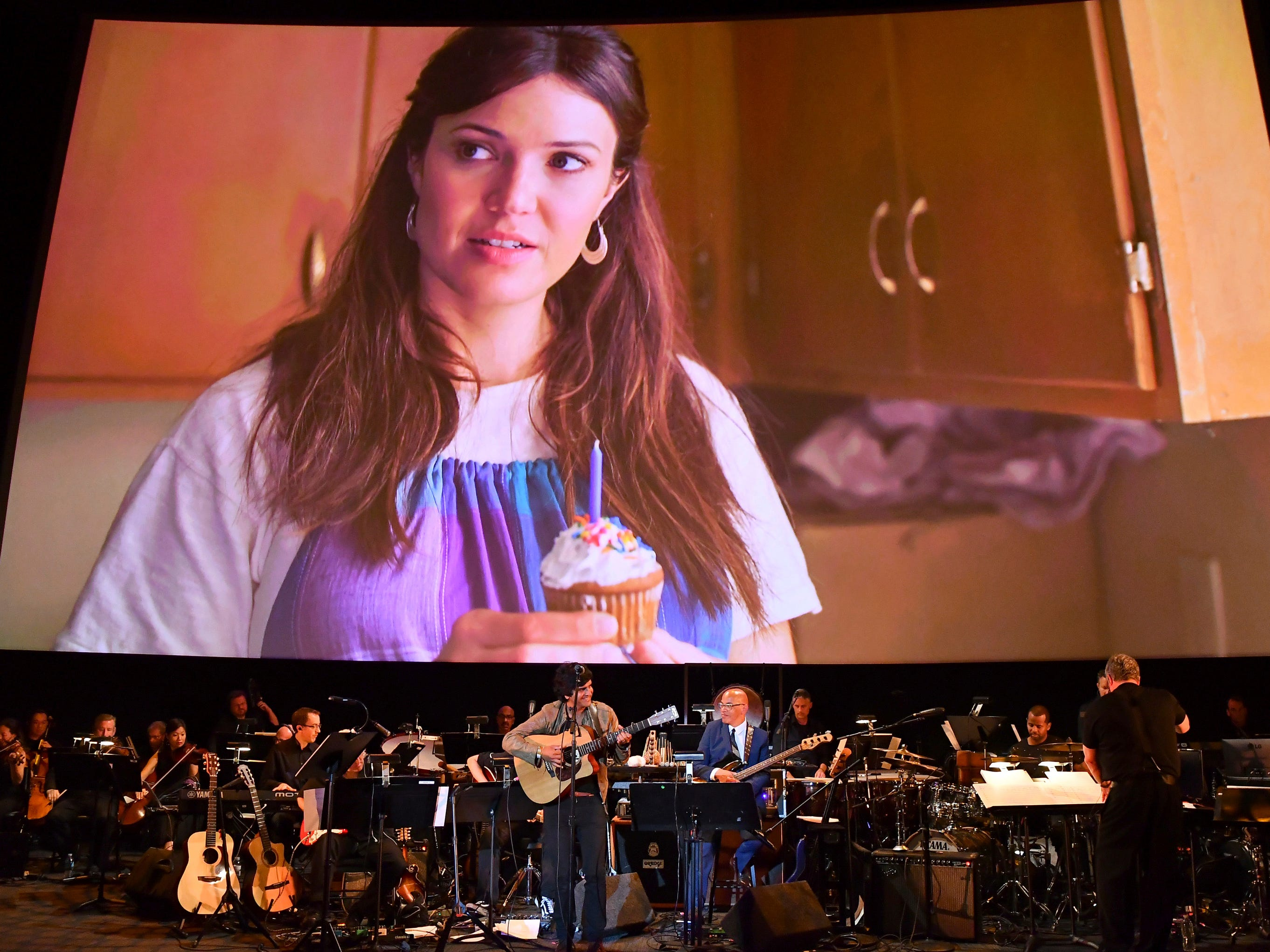 Conductor Mark Watters, right, and composer Siddhartha Khosla, center, perform the score from This Is Us during WORDS + MUSIC, presented Thursday, June 29, 2017 at the Television Academy's Wolf Theatre at the Saban Media Center in North Hollywood, Calif. Mandy Moore is pictured on screen. (Photo by Vince Bucci/Invision for the Television Academy/AP Images)