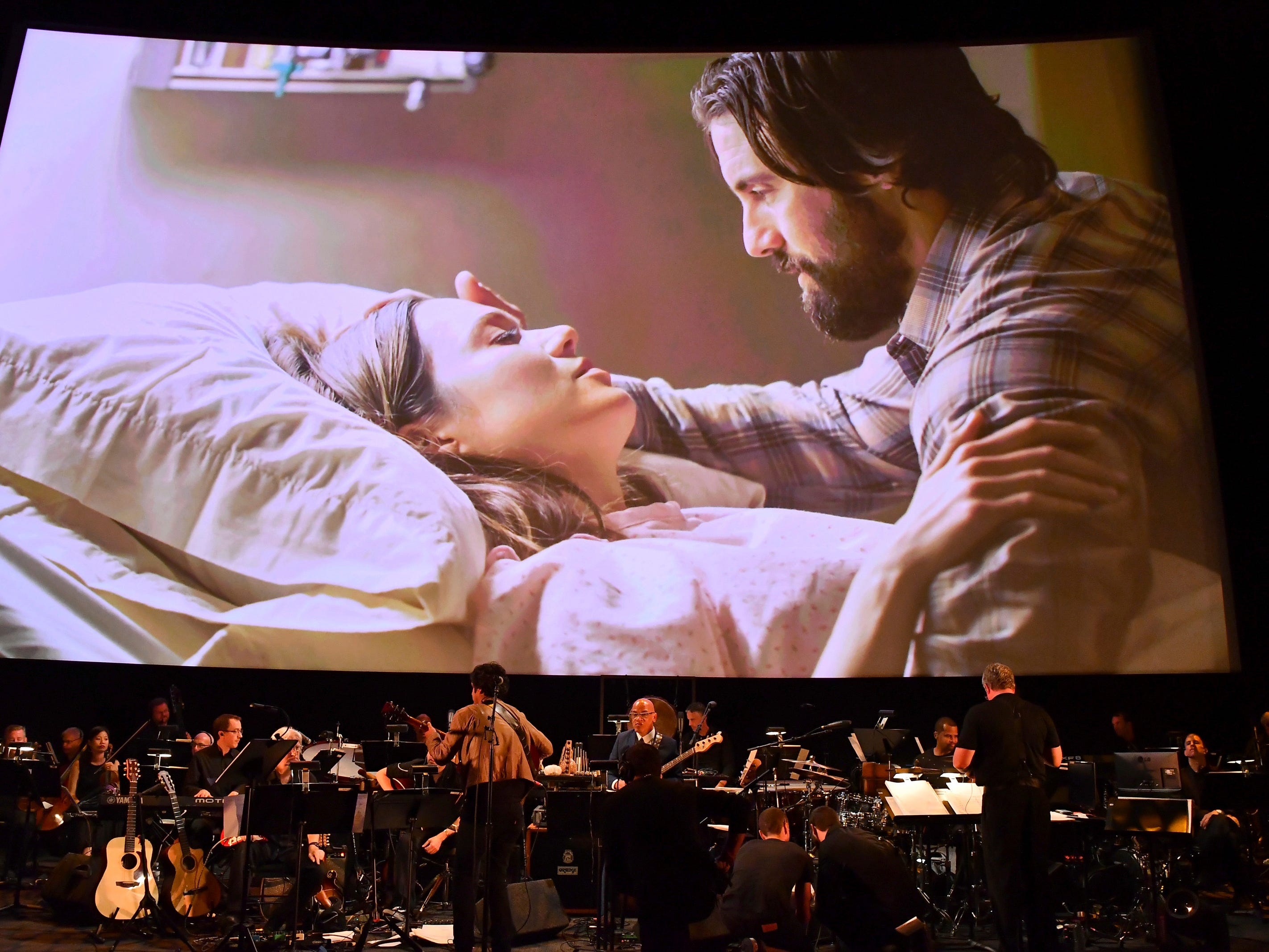 Conductor Mark Watters, right, and composer Siddhartha Khosla, center, perform the score from This Is Us during WORDS + MUSIC, presented Thursday, June 29, 2017 at the Television Academy's Wolf Theatre at the Saban Media Center in North Hollywood, Calif. Mandy Moore, left, and Milo Ventimiglia are pictured on screen. (Photo by Vince Bucci/Invision for the Television Academy/AP Images)