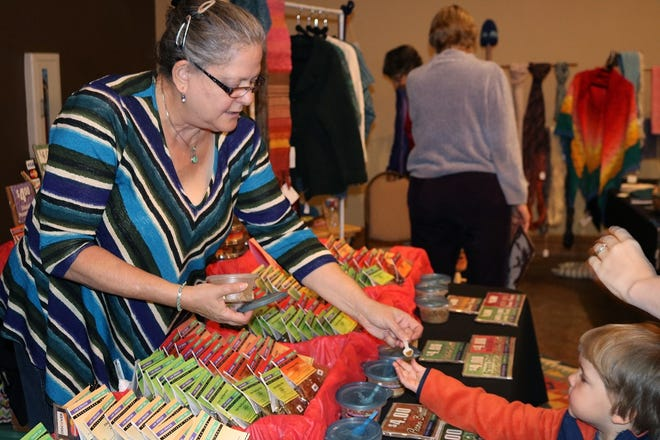 A vendor representing Las Cruces Candy Company hands out food samples to a child at HomeGrown: A New Mexico Food Show and Gift Market in 2016. This year's event will include more than 70 vendors representing a variety of food and beverage companies from around the state.