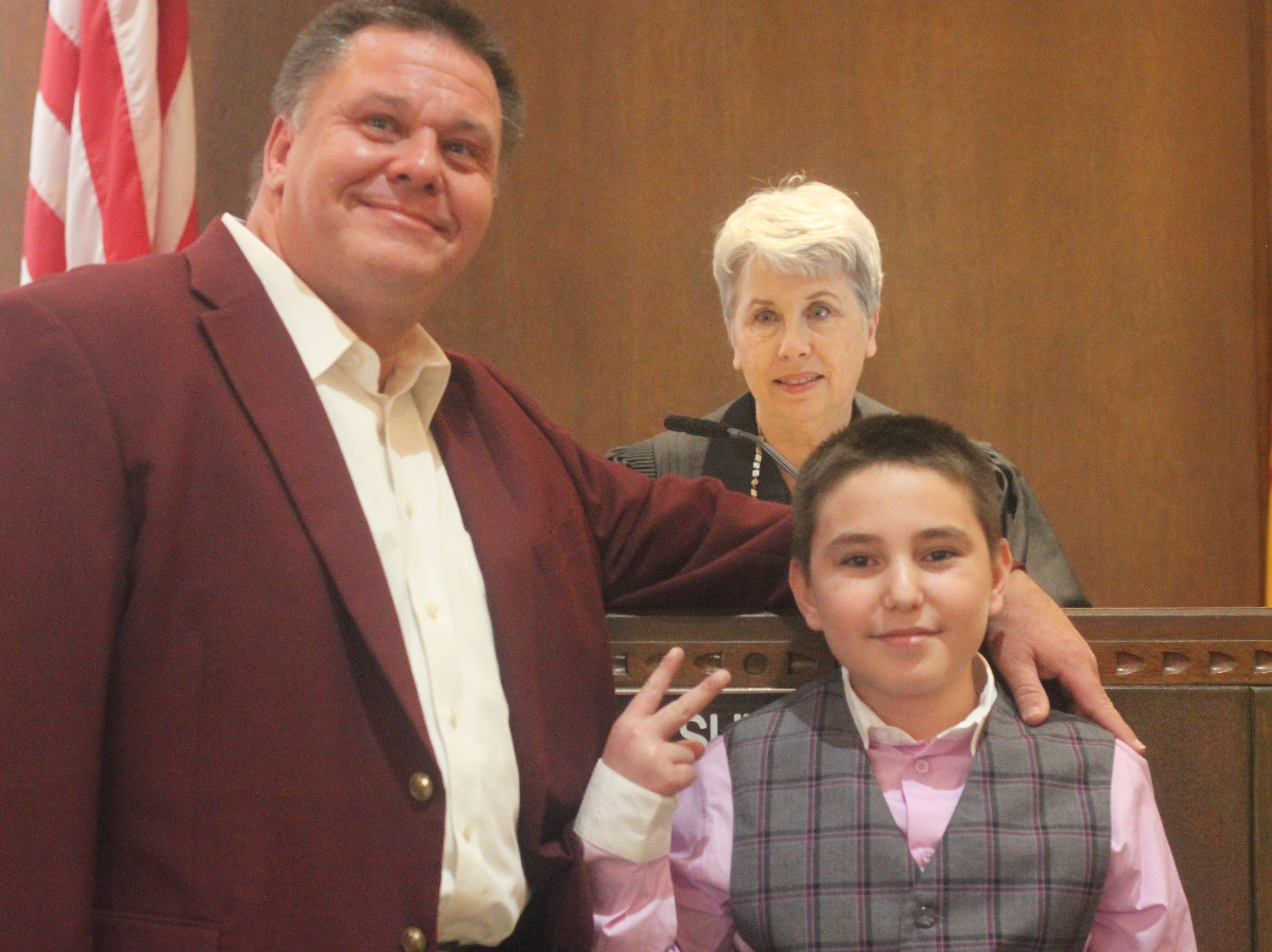 Nathaniel Zacek (right) celebrates his adoption to his father Glenn Zacek, Nov. 9, 2018 in the Eddy County Courthouse.
