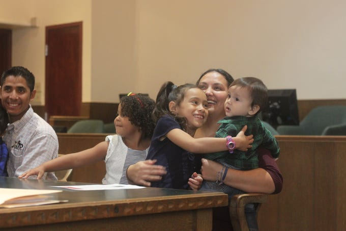 Jasmin Elizabeth Zarate (middle) embraces her new family after adoptions proceedings, Nov. 9, 2018 in the Eddy County Courthouse.