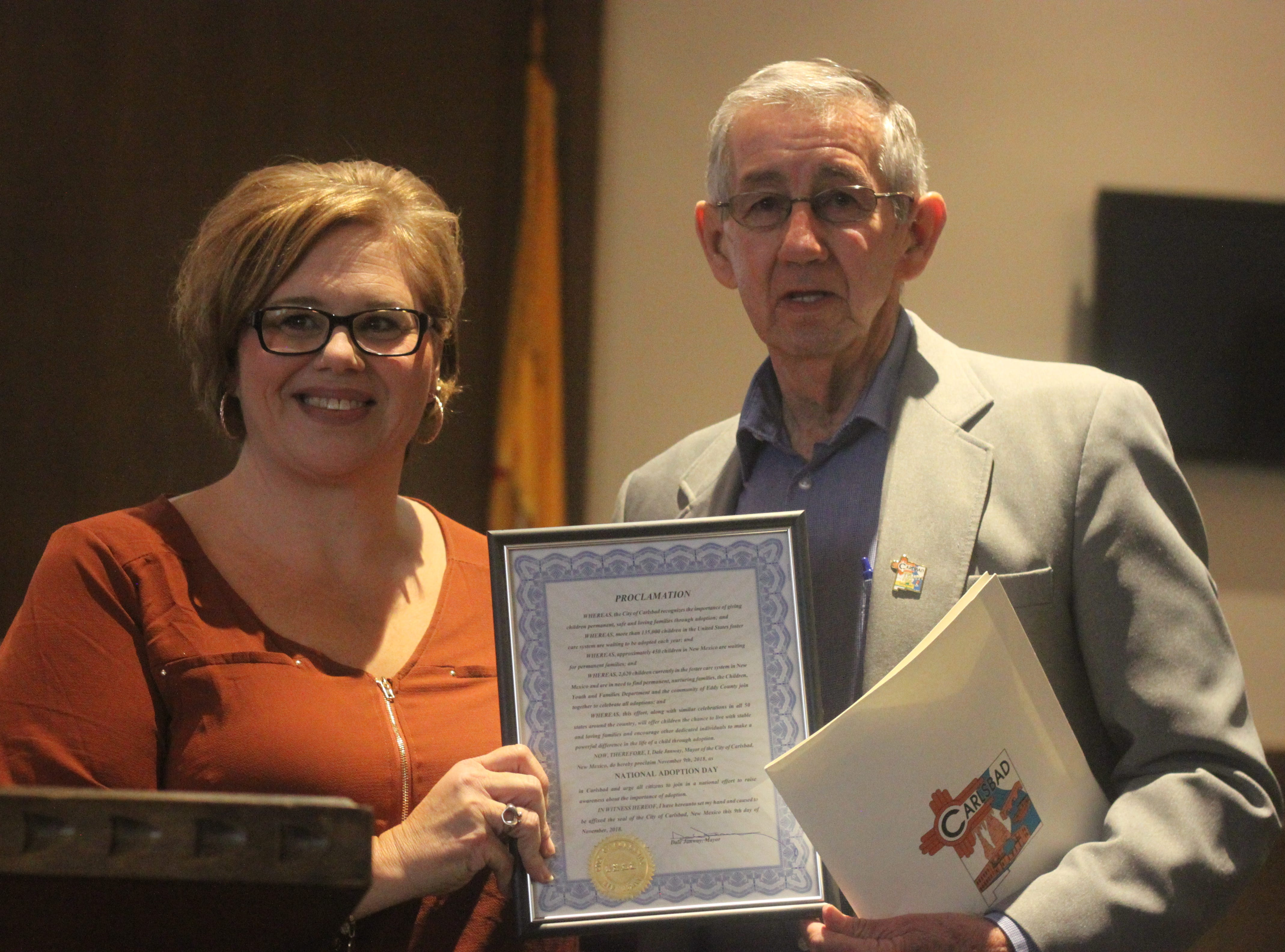 Carlsbad Mayor Dale Janway (right) presents a proclamation to Staci Compton, placement supervisor at the Children, Youth and Families Department, to commemorate adoption day, Nov. 9, 2018 in the Eddy County Courthouse.