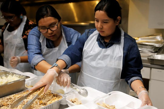 Navajo Preparatory School seniors Tayiah Lewis, left, and Samantha Yazzie help serve mashed potatoes and turkey for the Giving Thanks for Our Veterans event at the Farmington Indian Center on Friday.