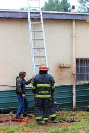 Ruidoso firefighters prepares to scale a ladder to investigate the roof after a fire had started in a chimney at the Re-Store shop, 2200 Sudderth Drive, around 11 a.m. this morning.