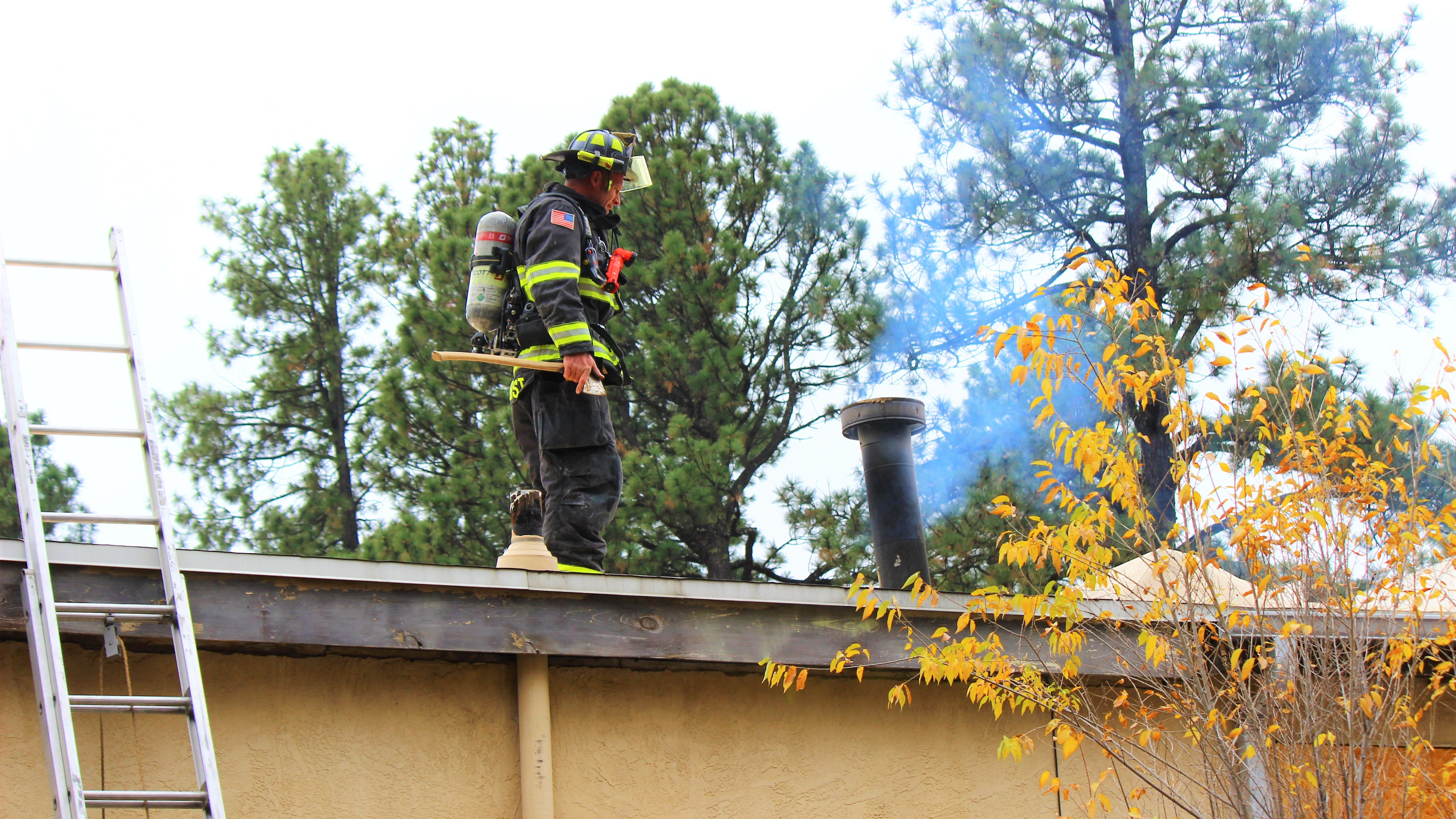 A Ruidoso firefighter investigate the roof of the Restore shop, 2200 Sudderth Drive, after a fire had started in the chimney earlier this morning.