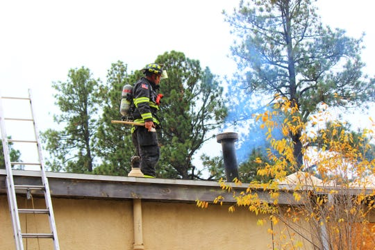 A Ruidoso firefighter investigate the roof of the Re-Store shop, 2200 Sudderth Drive, after a fire had started in the chimney earlier this morning.