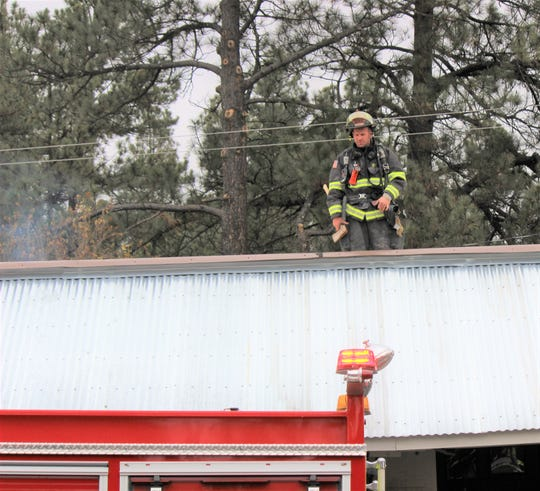 A Ruidoso firefighter investigates the roof of the Re-Store shop, 2200 Sudderth Drive, after a chimney fire had broken out after 11 a.m.