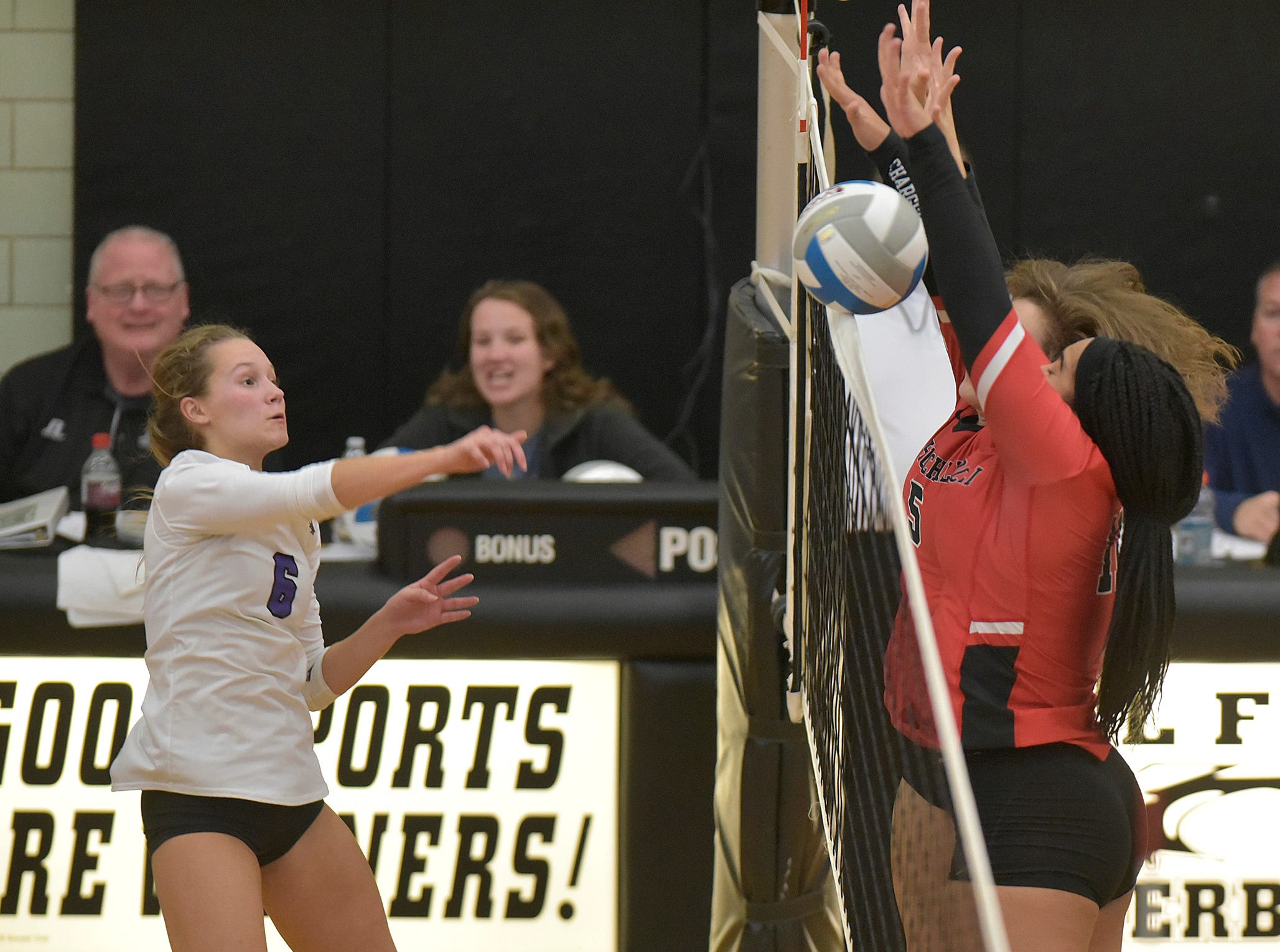 Woodhaven's Jenna Kekich (6) tries for the kill, but Maya Grant (11) and Grace Facione (5) deny the point.