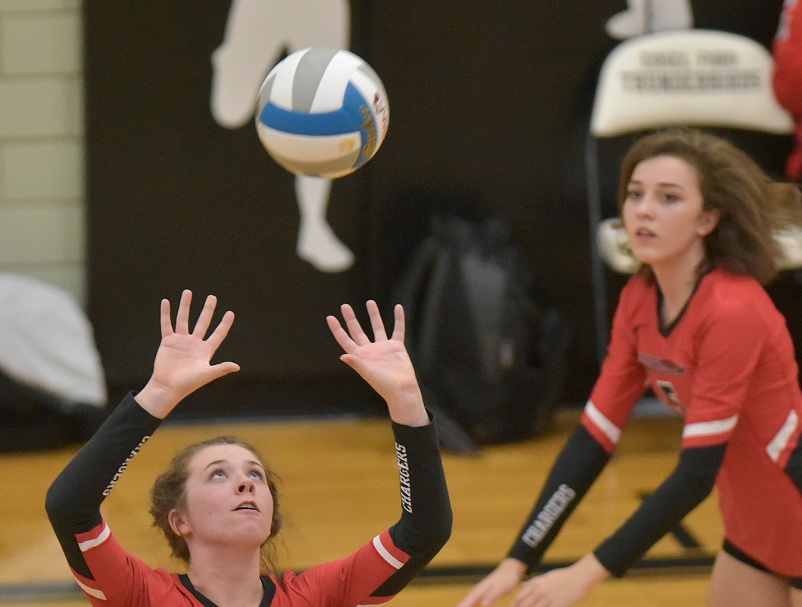 Grace Vaeth (1) sets the ball. Summer Clark (15) and Grace Facione (5), at right.