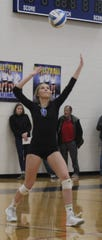 Marian senior Sarah Cavanaugh (9) lines up a serve in Thursday's Division 1 regional championship match against arch rival Mercy.