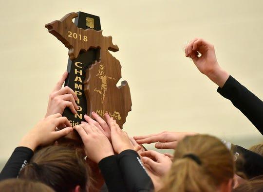 Churchill volleyball hoists the trophy high.