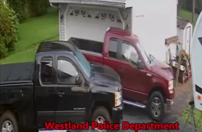Security video shows a man driving a red Ford F-150 leaving a home in Westland, where he earlier drove the truck into the parked black pickup and on into the yard, staying there for five hours.