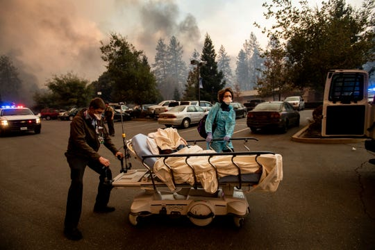 Medical personnel evacuate patients as the Feather River Hospital burns while the Camp Fire rages through Paradise, Calif., on Thursday, Nov. 8, 2018.