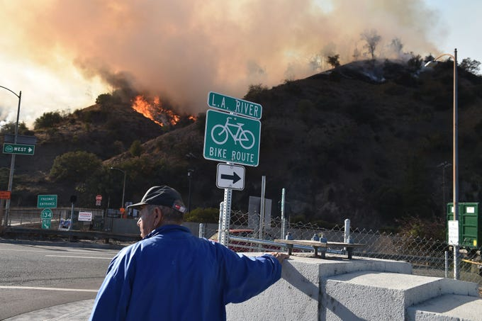 A man watches flames from a wildfire in Griffith Park in Los Angeles, California, November 9, 2018. - Staff at the Los Angeles Zoo, which is located in the park are preparing animals to be evacuated. (Photo by Robyn Beck / AFP)        (Photo credit should read ROBYN BECK/AFP/Getty Images)
