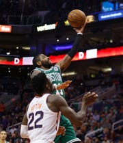 Celtics' Kyrie Irving (11) makes a layup against Suns' Deandre Ayton (22) during the second half at Talking Stick Resort Arena in Phoenix, Ariz. on November 8, 2018.