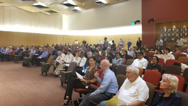 "Dozens of residents opposed to the Banner Health hospital attended the Chandler City Council meeting wearing stickers saying, ""Save our neighborhood."""