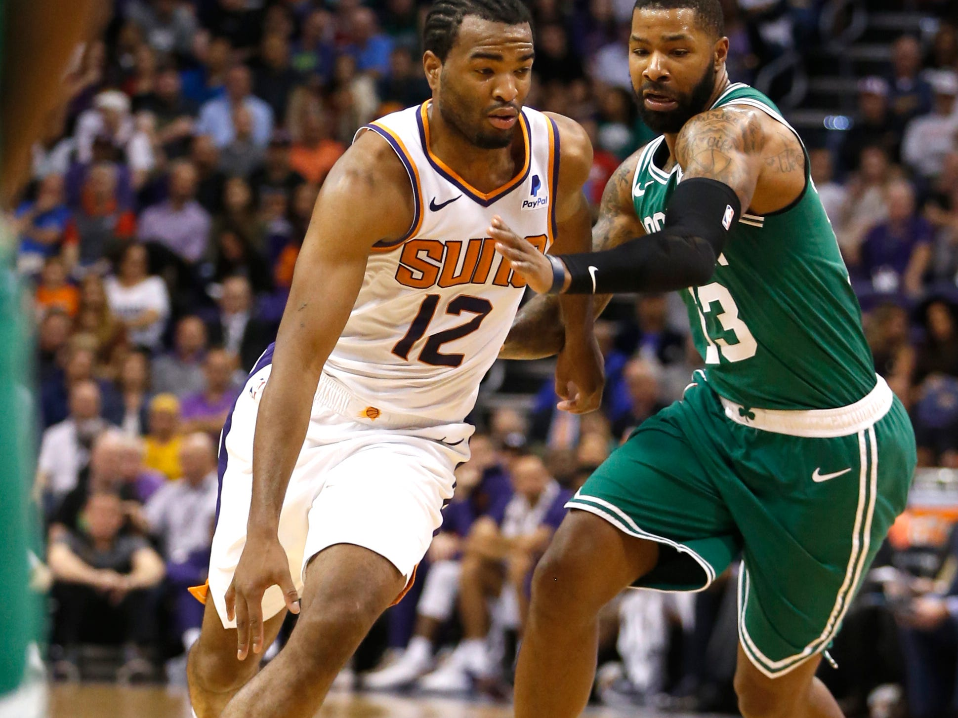 Suns' TJ Warren (12) drives against Celtics' Marcus Morris (13) during the first half at Talking Stick Resort Arena in Phoenix, Ariz. on November 8, 2018.