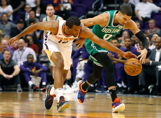 Suns' TJ Warren (12) attempts to steal a ball away from Celtics' Jayson Tatum (0) during the first half at Talking Stick Resort Arena in Phoenix, Ariz. on November 8, 2018.