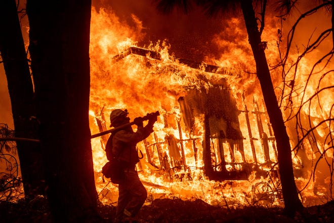 Firefighter Jose Corona sprays water Nov. 9, 2018, as flames consume from the Camp Fire consume a home in Magalia, California.
