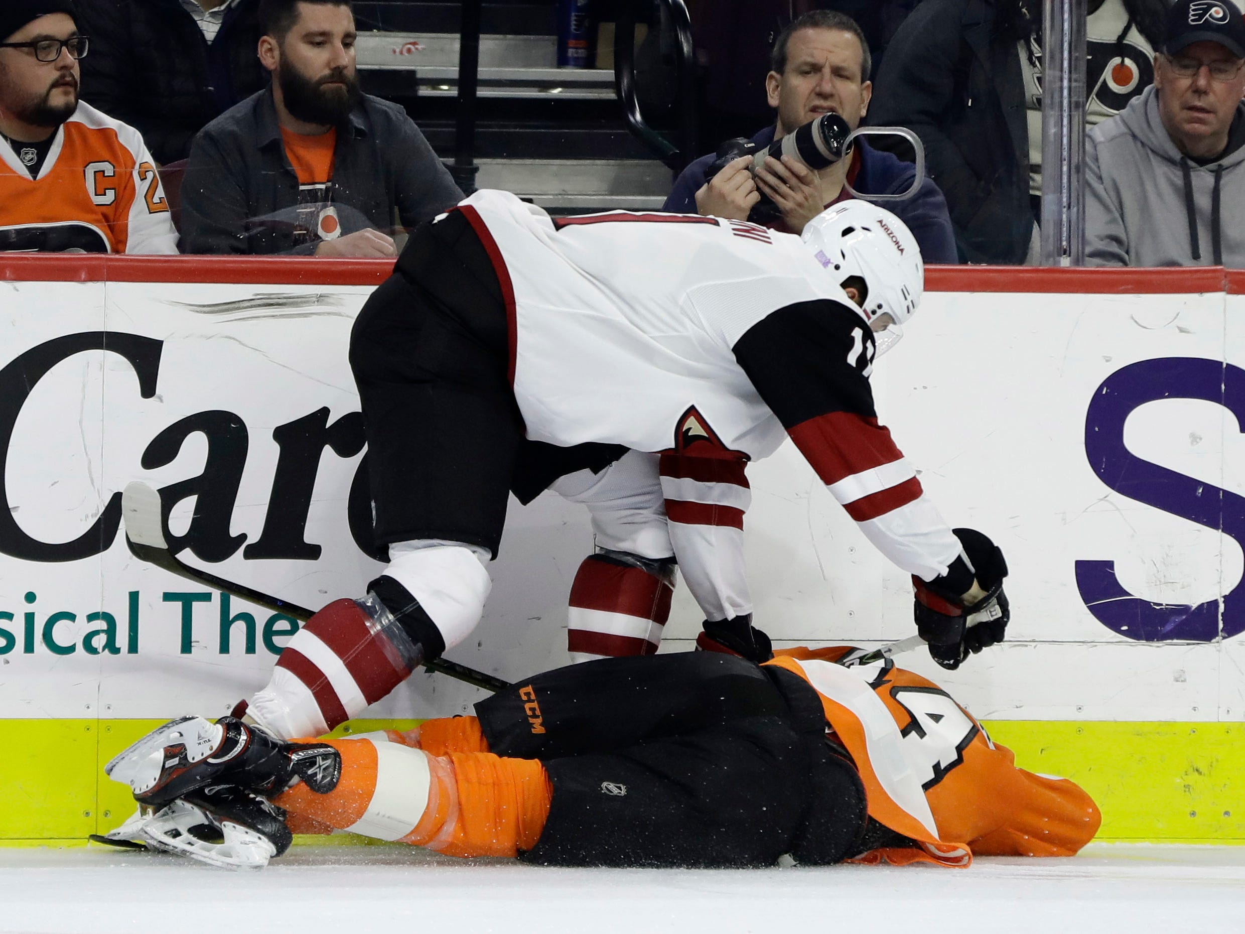 Arizona Coyotes' Brendan Perlini, top, pins Philadelphia Flyers' Sean Couturier to the ice during the second period of an NHL hockey game, Thursday, Nov. 8, 2018, in Philadelphia. (AP Photo/Matt Slocum)