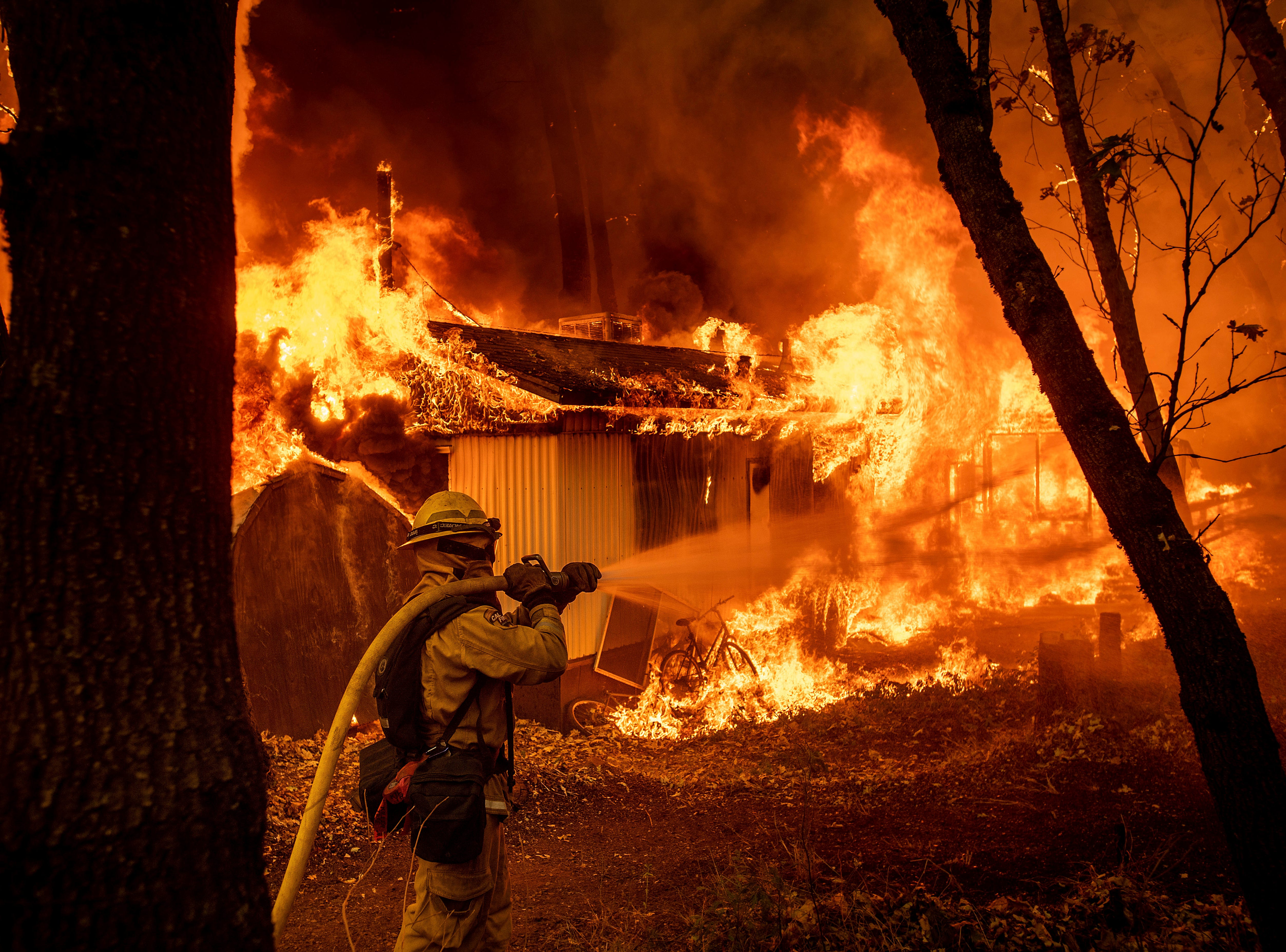 Firefighter Jose Corona sprays water Nov. 9, 2018, as flames from the Camp Fire consume a home in Magalia, California.