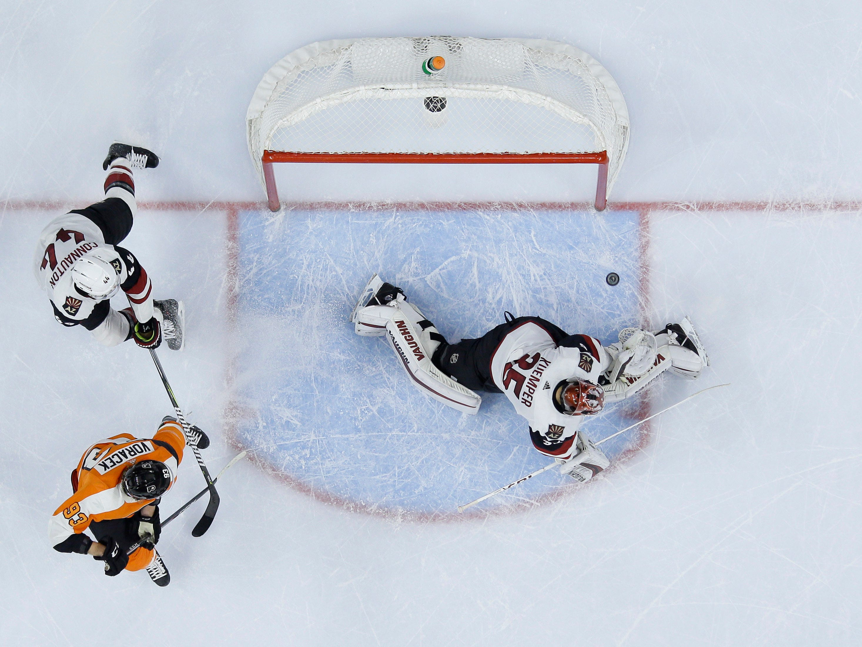 Arizona Coyotes' Darcy Kuemper (35) cannot block the game-winning goal by Philadelphia Flyers' Shayne Gostisbehere as Jakub Voracek (93) and Kevin Connauton (44) look on during overtime in an NHL hockey game, Thursday, Nov. 8, 2018, in Philadelphia. Philadelphia won 5-4. (AP Photo/Matt Slocum)