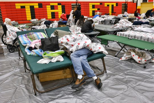 An evacuee from a wildfire rests on a cot covered under a blanket supplied by the Red Cross in the Taft Charter High School gymnasium in the Woodland Hills section of Los Angeles on Friday, Nov. 9, 2018. Portions of Southern California remain under siege as two large brush fires are threatening numerous communities. (AP Photo/Richard Vogel)