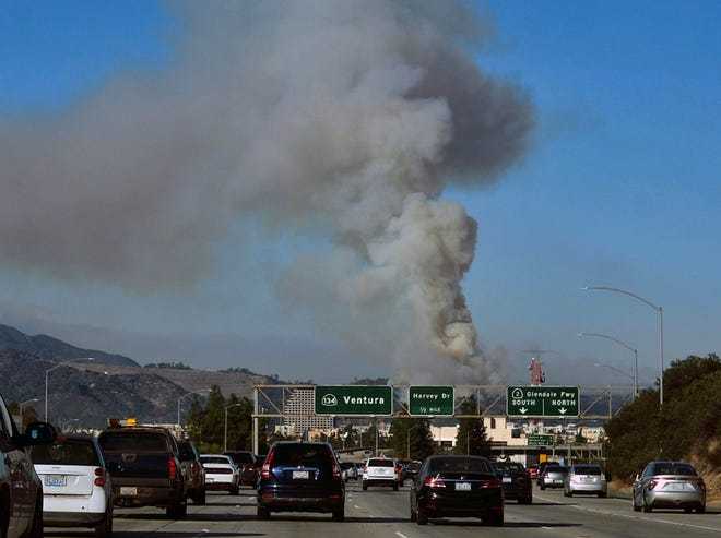 A large plum of smoke from a brush fire rises over interstate 5 outside of Griffith park in Los Angeles on Friday, Nov. 9, 2018. A wind-driven wildfire raged through Southern California communities on Friday, burning homes and forcing thousands of people to flee as it relentlessly pushed toward tony Malibu and the Pacific Ocean. (AP Photo/Ringo H.W. Chiu)