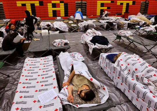 Evacuees from a wildfire rest on cots and blanket supplied by the Red Cross in the gymnasium at Taft Charter High School in the Woodland Hills section of Los Angeles on Friday, Nov. 9, 2018. (AP Photo/Richard Vogel)