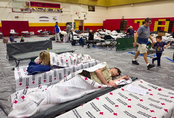 Evacuees from a wildfire rest on cots and warm themselves under blankets supplied by the Red Cross in the Taft Charter High School gymnasium in the Woodland Hills section of Los Angeles on Friday, Nov. 9, 2018. Portions of Southern California remain under siege as two large brush fires are threatening numerous communities. (AP Photo/Richard Vogel)