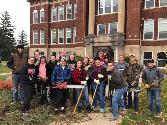 Sandusky students clear a patch of the Sanilac County Courthouse lawn that will host a new war memorial they are raising money for, on Nov. 4, 2018.
