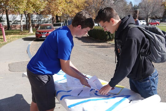 Hunter Grimm, 17, and another Reno High School student gather a petition to reinstate coach Dan Avansino following a walkout protest.