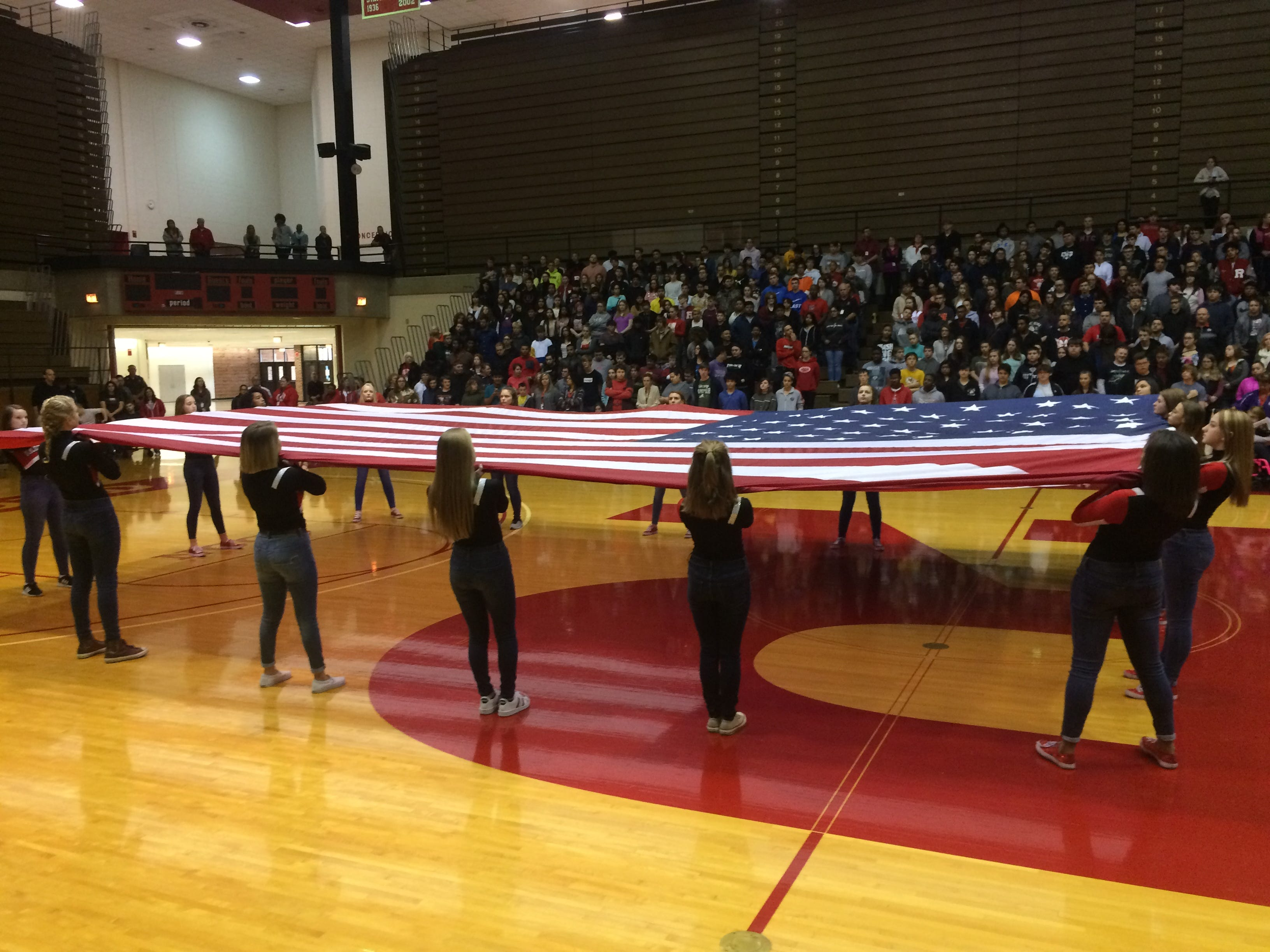 Members of the Richmond High School Devilettes hold a large flag during the playing of taps Friday in Tiernan Center.
