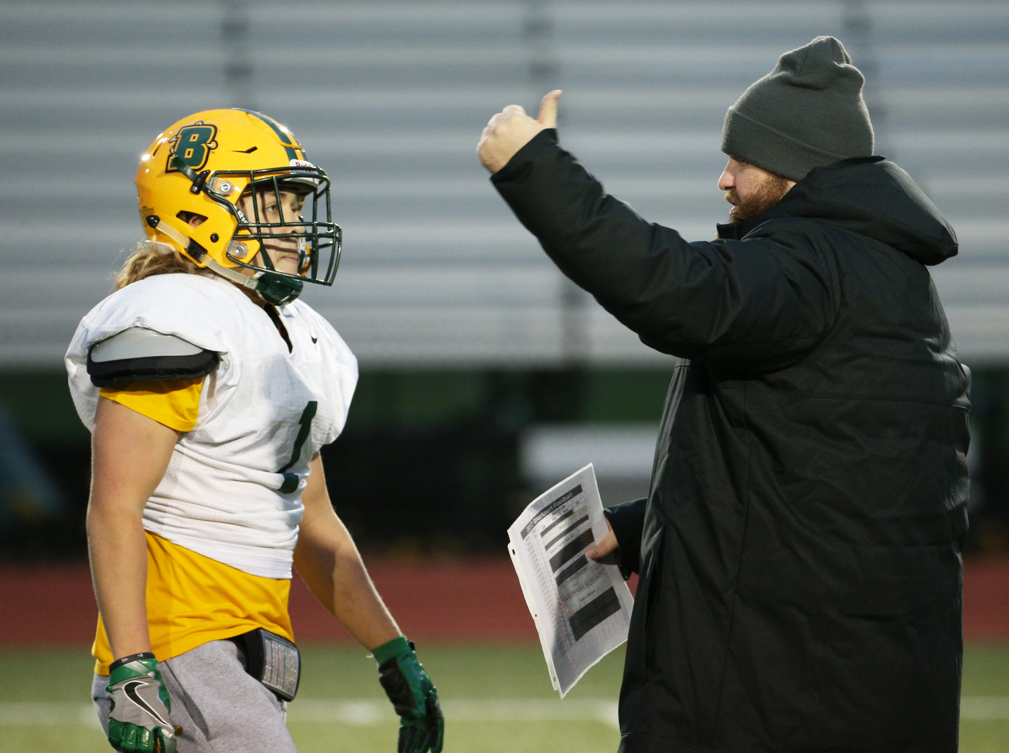 Senior running back Christian Hollister, left, of Perry, talks with assistant coach Justin Dueppengiesser at Brockport football practice.